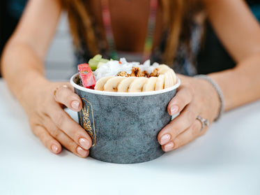 hands hold bowl full of fruit and granola