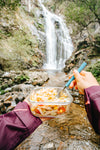 hands hold pasta salad and a fork by a waterfall outdoors