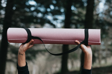 hands hold up a pink yoga mat outdoors