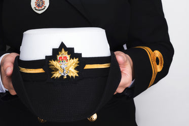 hands holding a navy peaked cap