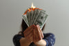 hands holding money aflame