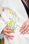 hands holds buttercup flowers in the pocket of their coat