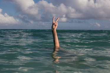hands peace sign in water