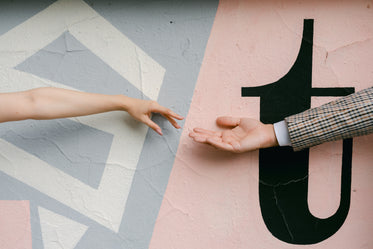 hands reach for each other against a painted wall