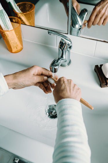 hands rinse out a wooden toothbrush in a white sink