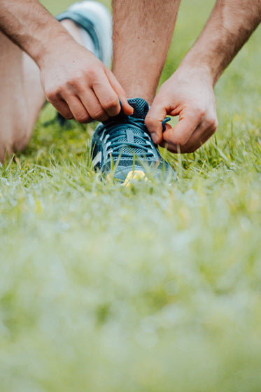 hands tying shoe laces on a running shoe