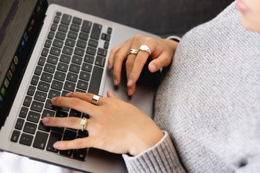 hands with gold rings type on a laptop