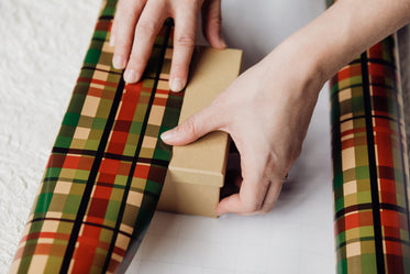 hands wrapping presents with paper