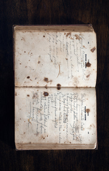 Handwritten Cookbook Lays Open To The Cake Section In A Wooden Surface
