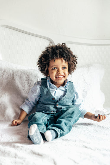happy little boy sitting on bed