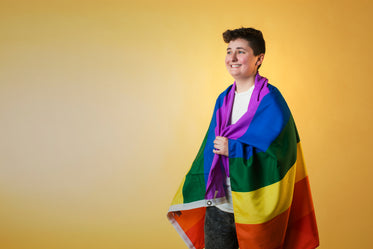 happy person wrapped rainbow flag