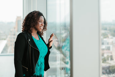 happy woman looking out woman from highrise office