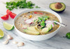 hearty bowl of vegetable noodle soup on marble counter