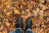hiker looks down at boots and leaves