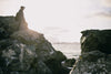 hiker stands on tall rock by ocean