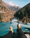 hiking shoes reach out to a cold aqua lake and rocky mountians