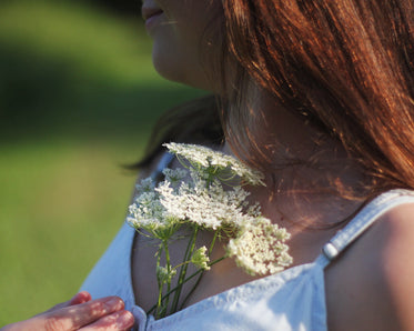 holding a bunch of queen annes lace to chest