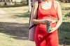 holding a yoga mat and water bottle in red workout gear