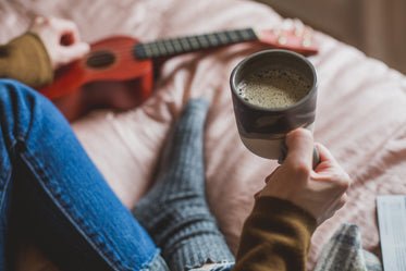 holding coffee in bed