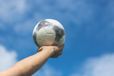 holding out soccer ball to the blue sky