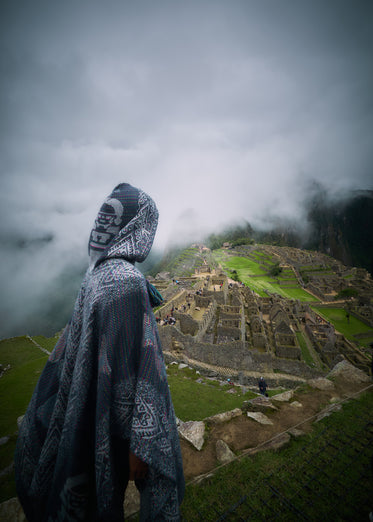 hooded person overlooking ruins