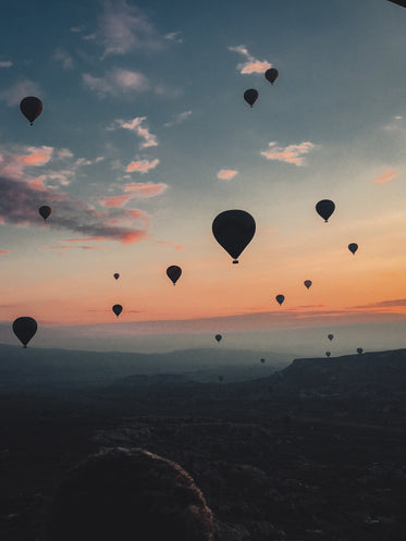 hot air balloons floating into the sunset