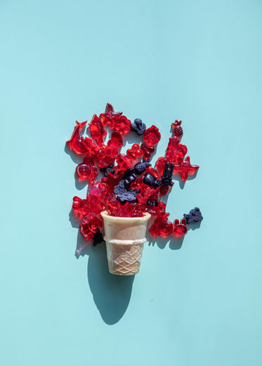 icecream cone with candy spilling out on blue background