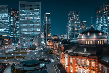 illuminated city building surrounded by high rises