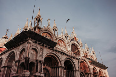intricately carved building with a bird flying overhead