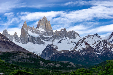jagged mountain peaks above lush forest below