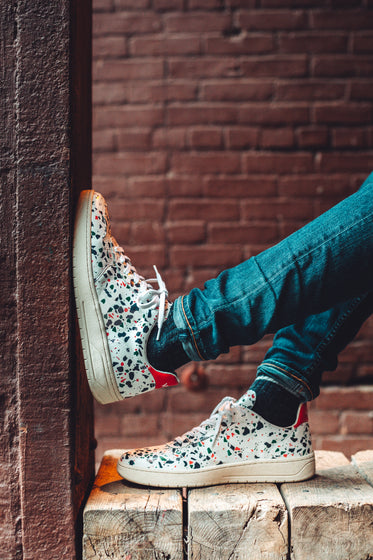 just chilling in white speckled fashion sneakers in alley