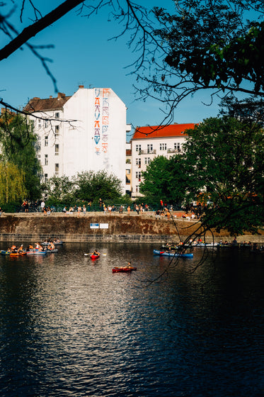 kayaks float in river with buildings behind it
