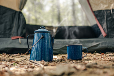 kettle and cup in front of tent