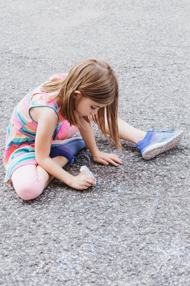 kid draws on ground with chalk