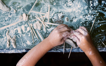 kids hands molding clay on a messy table top