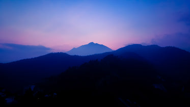landscape of blue hills and a pink sky at sunset