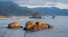 large boulders emerge from water at the shoreline