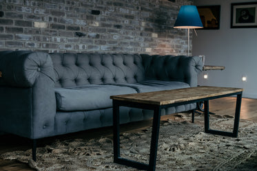 large grey sofa by brick wall