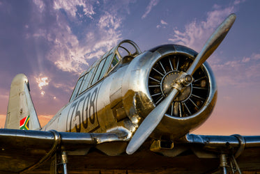 large silver plane at sunset with large propellers