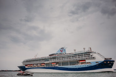 large white and blue cruise ship on a cloudy day