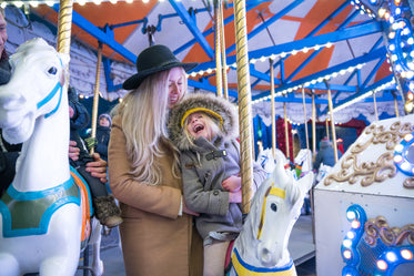 laughing girl and mom on carousel