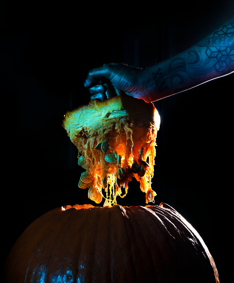 Lifting The Top Off Of A Freshly Carved Pumpkin