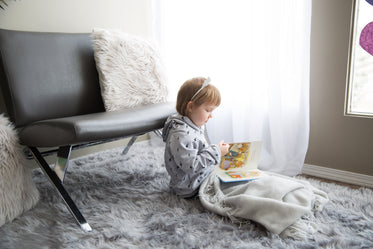 little girl under a blanket reading