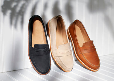 loafers leaning along white wall