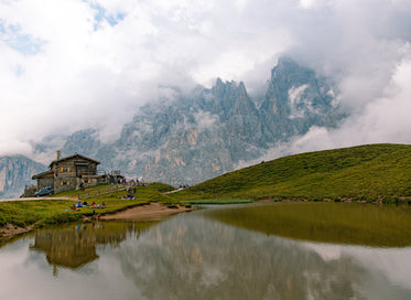 log cabin reflected in pond backed by mountains