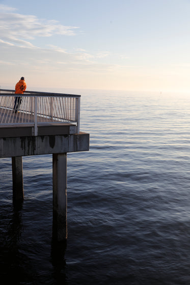 lone man stands on a pier at sunset