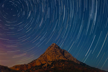 long exposure at night of streaking stars against landscape