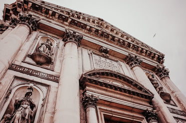 looking up a buildings with alcoves and sculptures