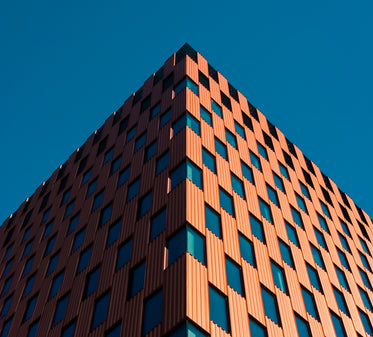 looking up the the corner of a checkered building