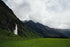 lush green fields by mountains and waterfall